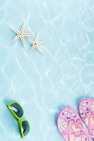 two starfishes, sunglasses and flip flops under water on blue background Stock Photo
