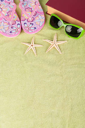 green beach towel with several summer stuff photo