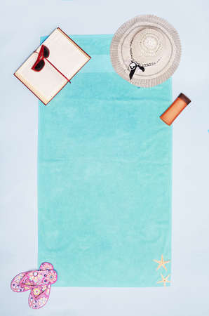 concept with a turqoise beach towel and summer stuff on blue background with copy space