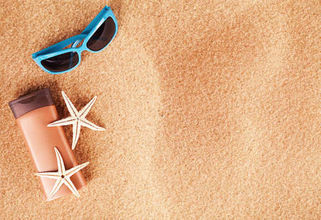 seasonal concept with two starfishes and sandals on sand Stock Photo - 20972253