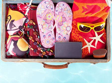 open suitcase: top view of a suitcase with full of summer stuff on blue background