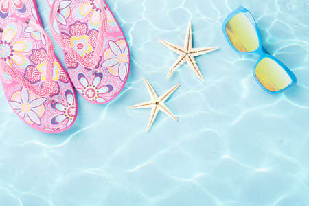 two starfishes, sunglasses and flip flops under water on blue background Stock Photo - 20972273