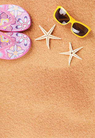 seasonal concept with two starfishes and sandals on sand Stock Photo - 20972301