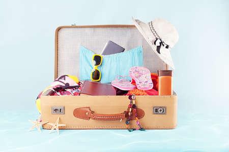 pasaporte: maleta retro con lleno de ropa, libros y pasaporte en fondo azul Foto de archivo