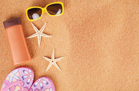 seasonal concept with two starfishes and sandals on sand Stock Photo - 20972347