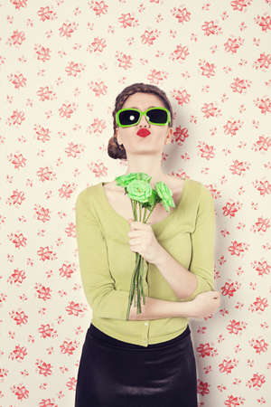retro style woman holding green roses blowing a kiss in front of a vintage flowered wall background photo