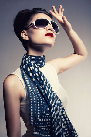 young brunette model wearing a sunglasses and a scarf posing on gray background photo