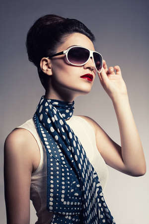 young beautiful fashion model with a spotted blue scarf posing on gray background