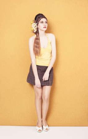 팬티 스타킹: 체크 무늬 스커트는 노란색 배경에 포즈 젊은 아가씨