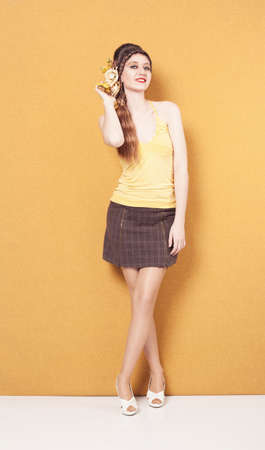 checkered skirt: smiling young beautiful lady with flowers on her braided hair looking at camera on yellow background Stock Photo