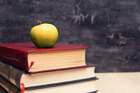 stack of books and a green apple infront of a blackboard