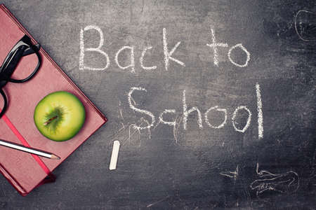back to school concept with various staff on blackboard background photo