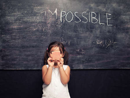 conceptual cute: very cute little girl holding an eraser in front of a blackboard