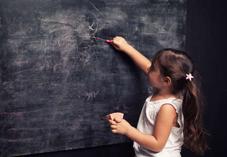 cute little girl writing something with a pink chalk on blackboard Stock Photo