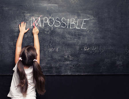 optimist: cute little girl putting a cross over impossible on blackboard