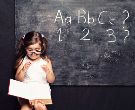 little girl barefoot: smart little girl reading a book in front of a blackboard Stock Photo