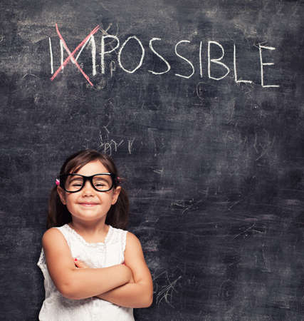 optimist: smart little girl smiling in front of a blackboard Stock Photo