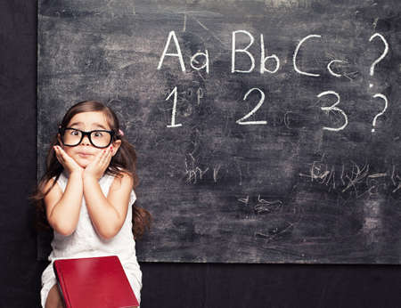 funny little squint eyed little girl posing sitting in front of blackboard Stock Photo