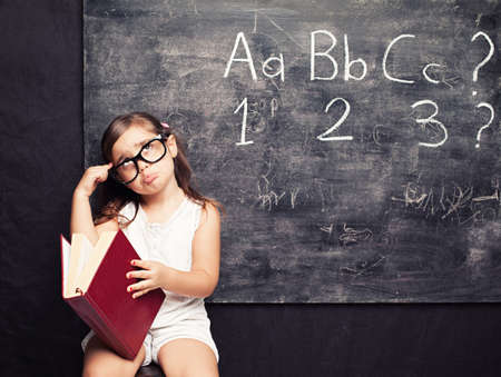 little cute girl holding a red book thinking in front of a blackboard photo