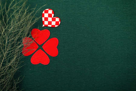 red hearts and a green plant on green background photo