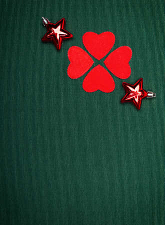christmas ornaments and a clover made of red hearts on green background photo