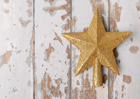 gold shiny star shaped christmas ornament on white old wooden background Stock Photo - 23148601