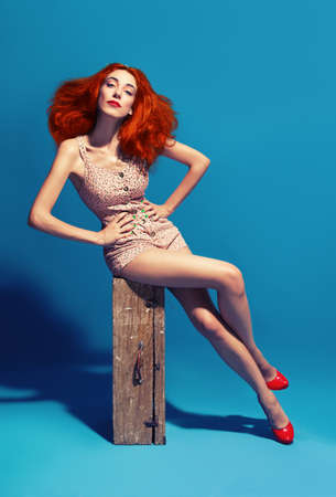 red haired lady wtih retro swimsuit sitting on vintage suitcase on blue background photo