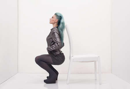 young lady with grey leather jacket posing in a white room with a white chair photo
