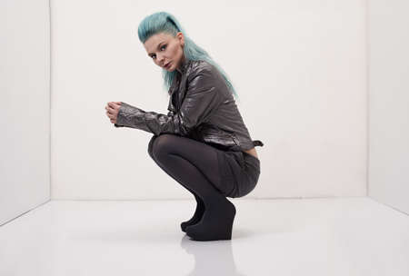 young model with blue hair wearing a grey leather jacket posing photo