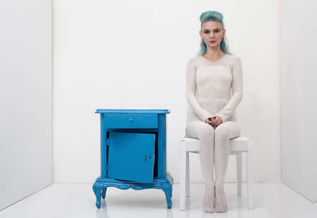 nightstand: young lady posing in a white romm with a damaged retro nightstand Stock Photo