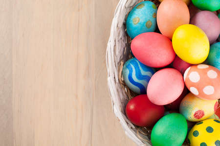 colorful still life: colorful easter eggs in a basket on wooden background