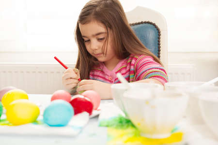 very cute little girl making colorful eggs for easter photo