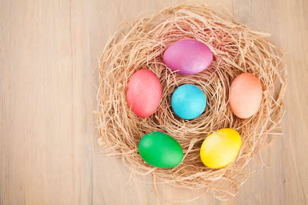 easter nest: colorful easter eggs on a wooden table Stock Photo