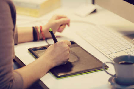 graphic designers: a graphic designer is working and using a graphic tablet