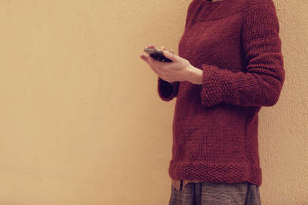filtered photo of an young woman holding a smart phone and touching the screen with her finger photo