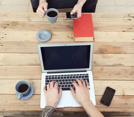 tattoed: chico joven con el brazo tatuado con un ordenador port�til mientras que su amigo usando un tel�fono inteligente