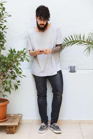 tattoed: chico joven con el brazo tatuado utilizando un tel�fono inteligente
