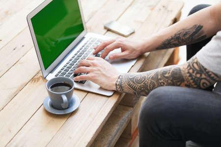 tattoed: chico inconformista con el brazo tatuado utilizando un laptop.focus en la mano