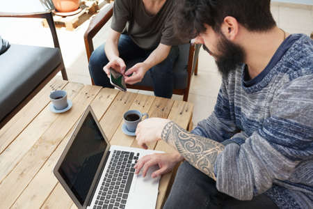 tattoed: two friends looking at the screen of a smart phone Stock Photo