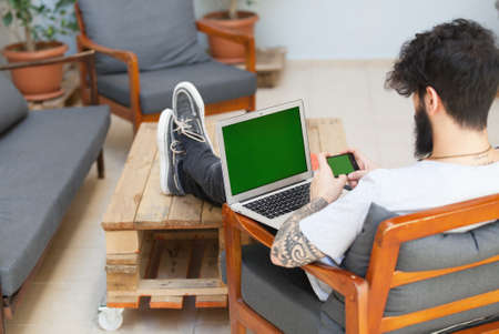 tattoed: young hipster guy using a laptop and a smart phone.focus on the phone
