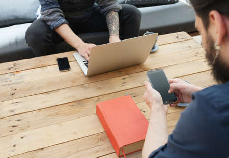 tattoed: two young man using laptop and a smartphone.focus on the phone Stock Photo