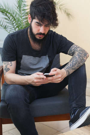 tattoed: young guy with beard and tattooed arm using a smartphone Stock Photo