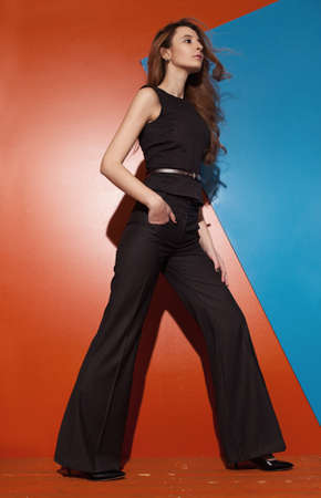 long pants: beautiful young woman wearing bellbottomed, high waisted pants on red background