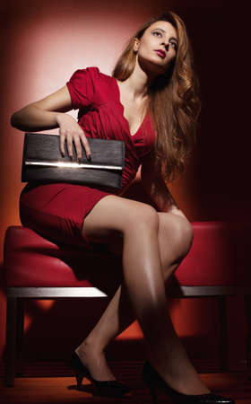 mini dress: young woman wearing red night dress on red background
