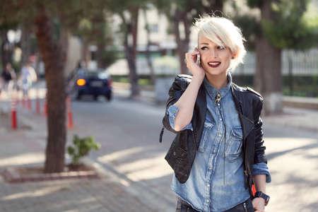 chaqueta de cuero: retrato de un estilo de punk joven mujer rubia al aire libre, hablando con su teléfono móvil