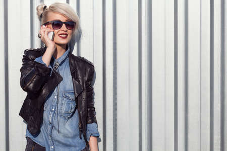 lady on phone: young punk style blond lady leaning on wall and using her mobile phone