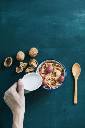cereal: desayuno con copos de maíz y leche en la mesa de madera oscura Foto de archivo