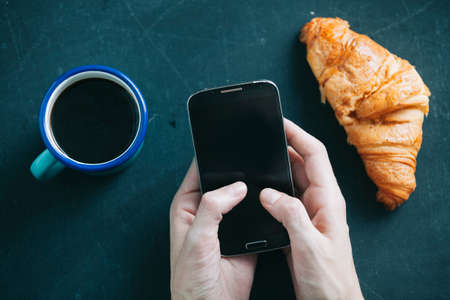 beverage display: coffee break with Croissant while using mobile phone
