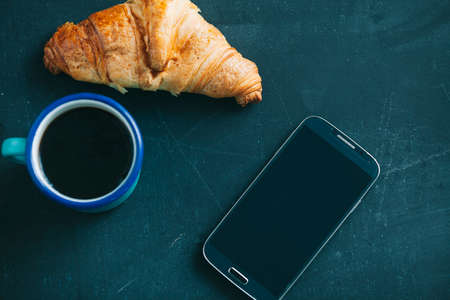 beverage display: breakfast with Croissant and coffee on dark wooden table