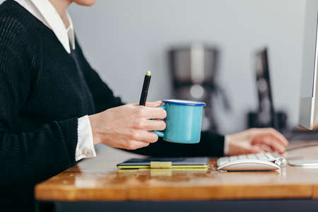 homely: young woman working in a homely office with her coffee and stuff Stock Photo